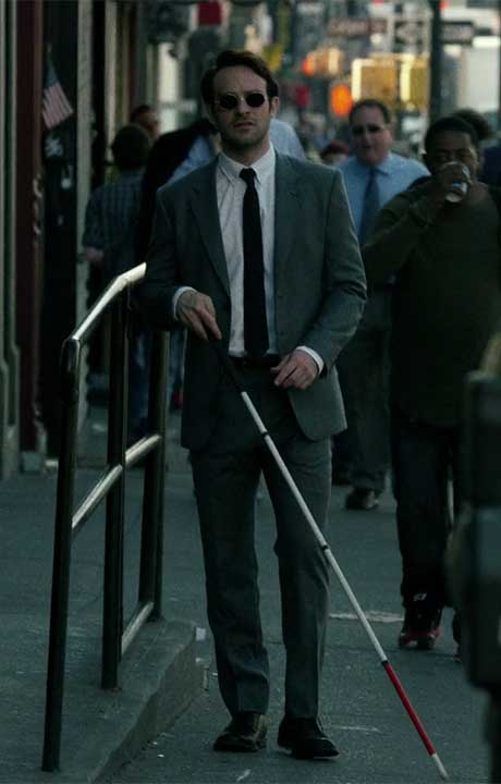 Matthew Murdock walking down sidewalk with Cane Sunglasses and Grey Suit